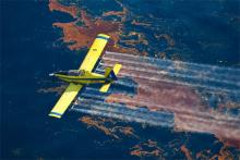 Yellow aeroplane flying over an oil slick spraying dispersant