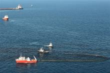 Group of vessels and a boom attempting to clean up spilled oil from the surface of the ocean