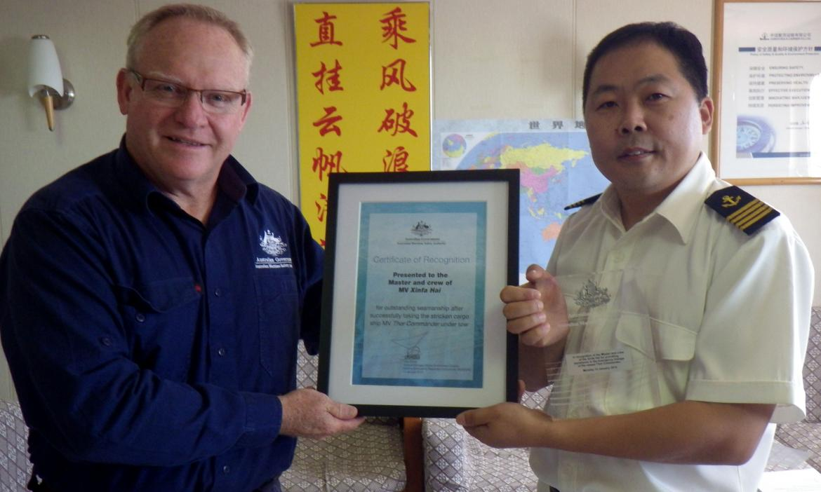 AMSA Surveyor Greg Collinson presents Captain Li with the certificate and plaque