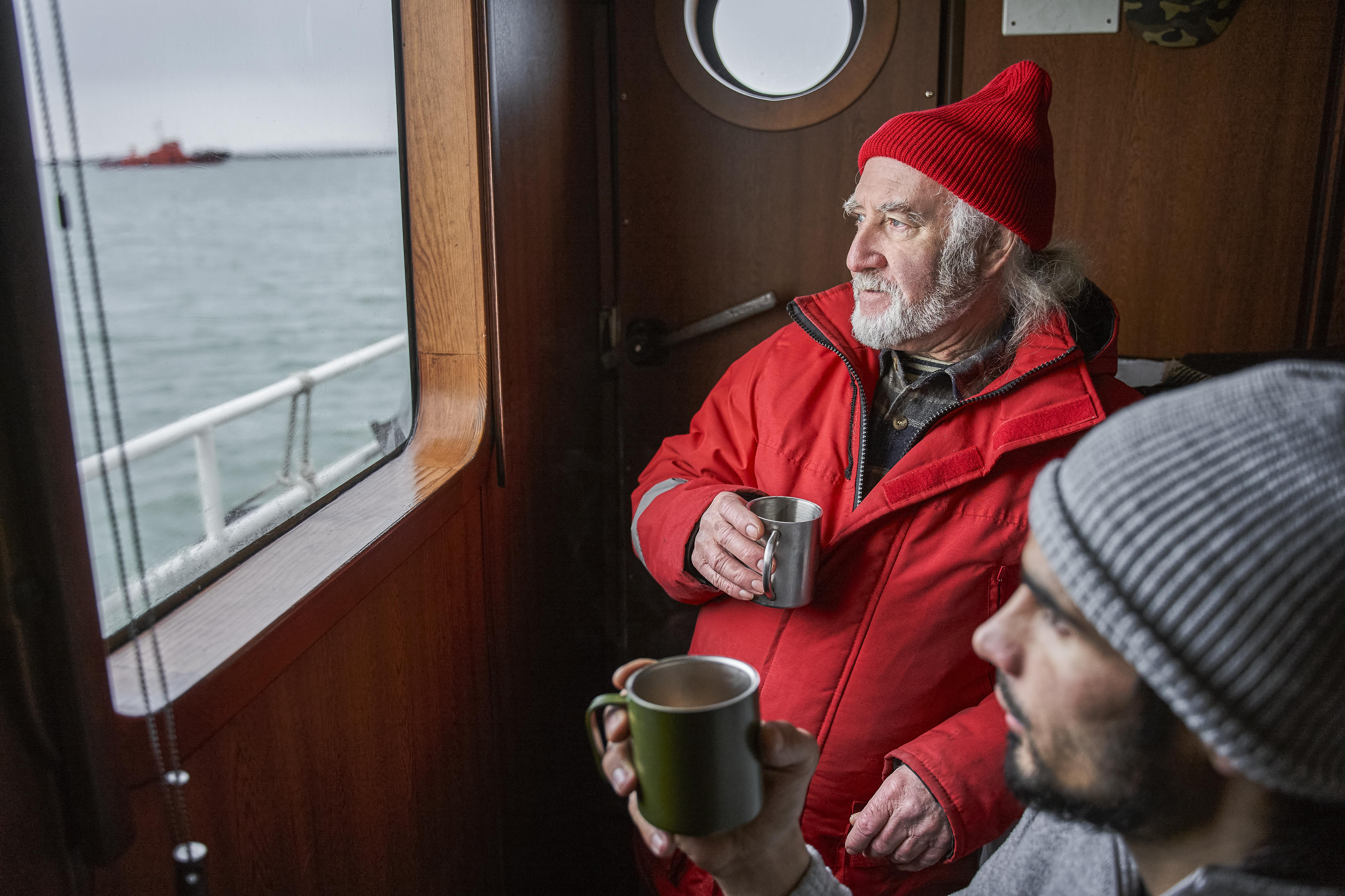 Two seafarers having a coffee looking out to sea