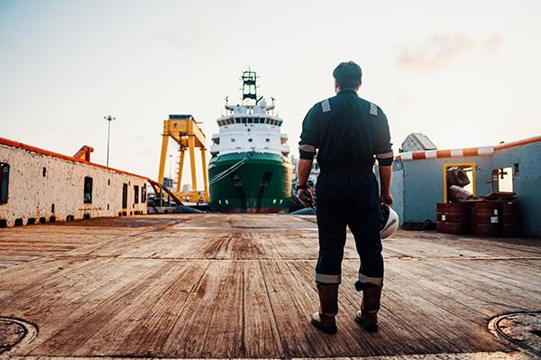 Seafarer looking out from the port to a vessel leaving port