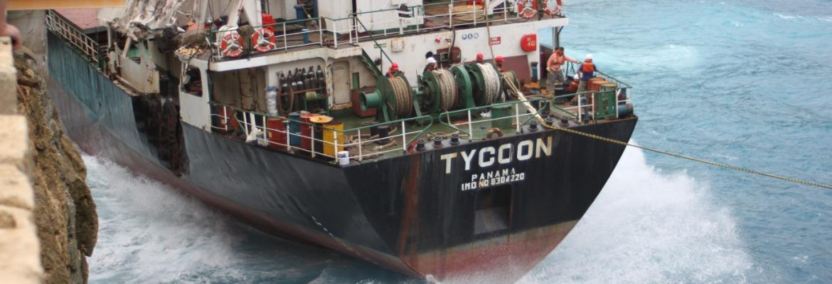 Image of MV Tycoon being washed against cliffs