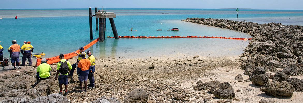 People looking out from the shore at Port Moresby and a containment boom