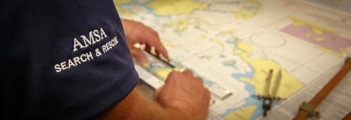 Looking over a search and rescue officers sleeve at a map with navigation equipment