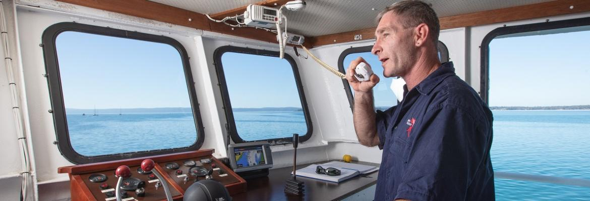 man speaking into a radio on a vessel