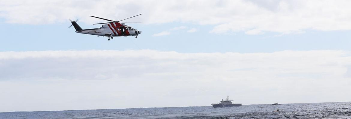 Helicopter in sky and vessel on water