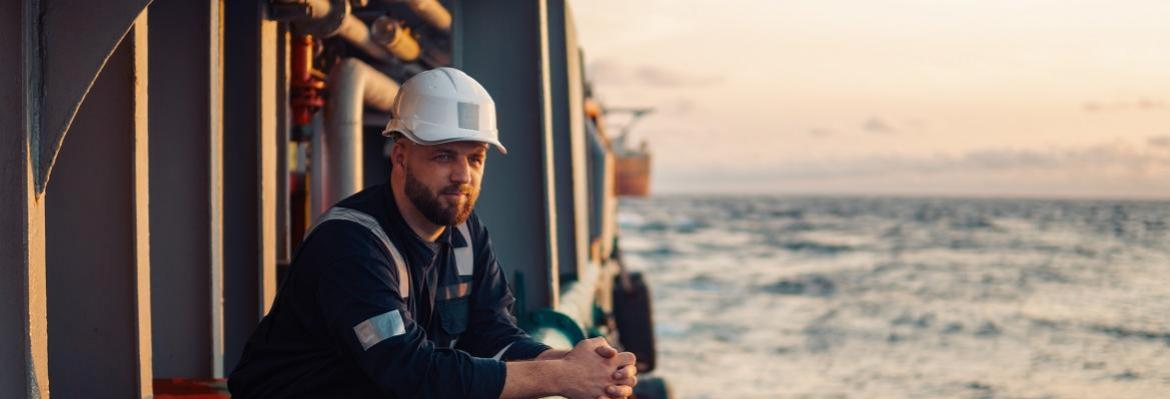 seafarer peers over water from ship