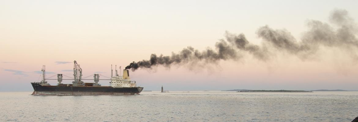 Ship in the middle of the ocean in front of a sunset with smoke billowing out
