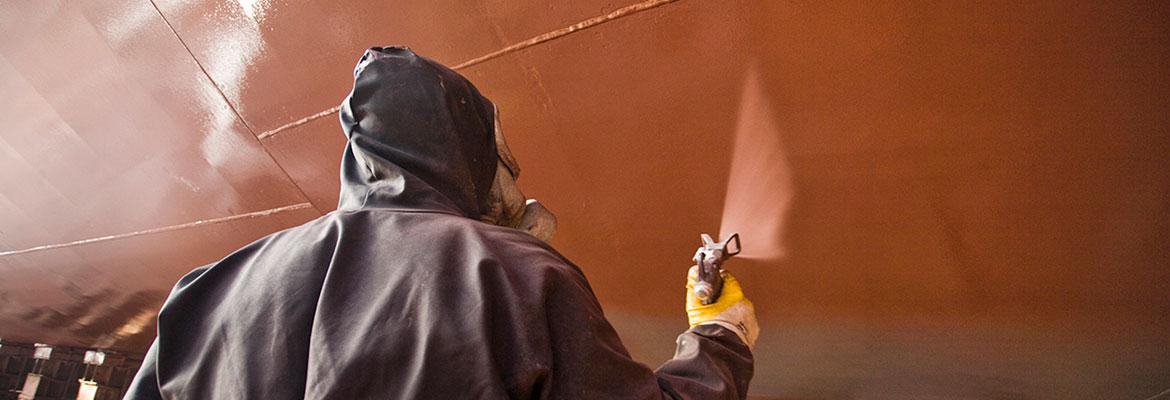 Person in a spray painting suit spraying the hull of a vessel