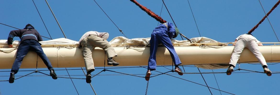 people hanging off a boom on a ship