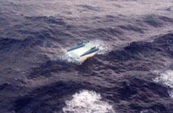 Image of upturned catamaran (believed to be SV Moorings)
