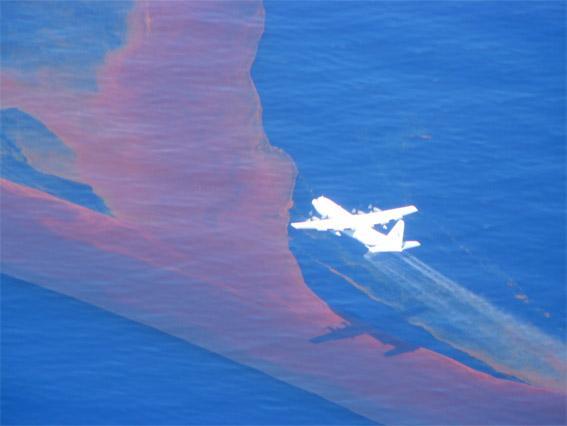 Image of aeroplane flying over an oil slick spraying dispersant