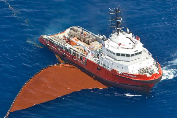 Image of a ship with a boom attempting to recover the rust-coloured oil captured on the surface of the water